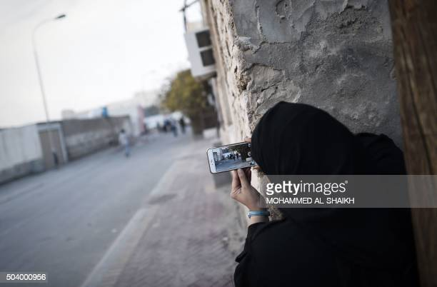 A Bahraini woman uses a mobile phone to take photos during clashes with riot police in the village of Sitra south of the capital Manama on January 8...