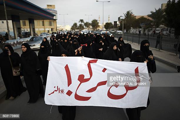 Bahraini women hold a banner during a protest in the village of Jidhafs west of Manama against the execution of prominent Shiite Muslim cleric Nimr...