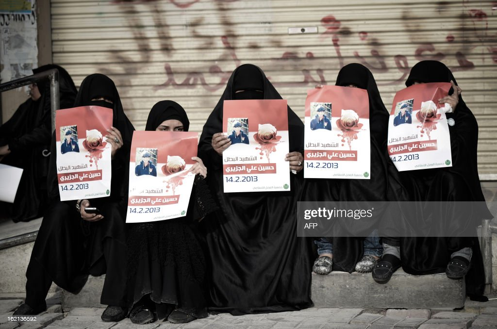 Bahraini women hold placards as they take part in a memorial service for teenager Hussein al-Jazeeri (Jazizi) which later erupted into clashes with riot police in the village of Daih, west of Manama, on February 19, 2013. The 16-year-old was killed in Daih on February 14, during protests marking the second anniversary of the Shiite Muslim-led uprising.