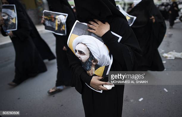 Bahraini women hold posters bearing portraits of prominent Shiite Muslim cleric Nimr alNimr during a protest against his execution by Saudi...
