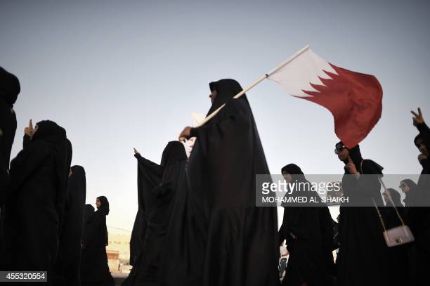 Bahraini women hold up the national flag and gesture during an anti-government protest in the village of Sitra, south of Manama, on September 12,...