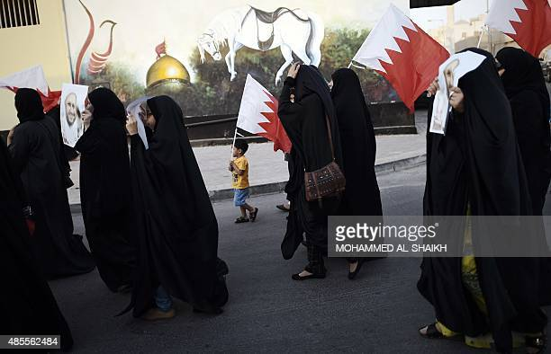 Bahraini women protesters and a child hold placards bearing the portraits of Jailed former MP Sheikh Hassan Isa and Sheikh Ali Salman head of the...