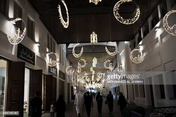 Bahrainis walk near the shops at the old manama market in the Bahrain capital city of Manama late on June 10 2016 during the Muslim holy month of...