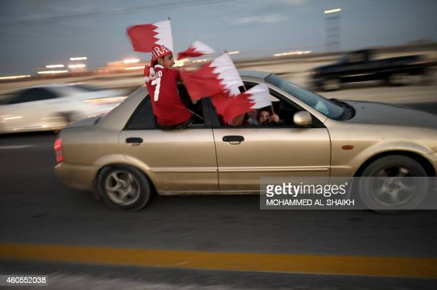Bahrainis wave their national flag as they drive down a street celebrating Bahrain National Day in Sakhir south of Manama on December 16 2014 AFP...