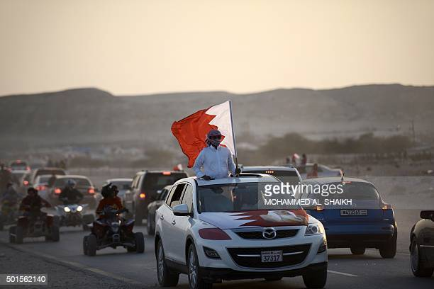 Bahrainis wave their national flags as they drive down a street celebrating Bahrain National Day in Sakhir south of Manama on December 16 2015 AFP...