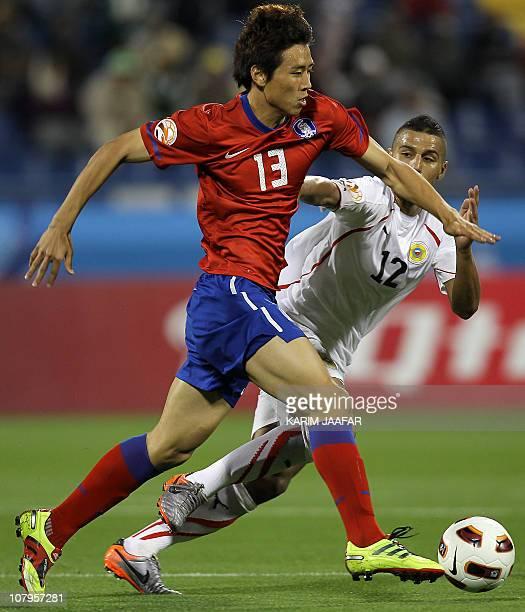 Bahrain's midfielder Fawzi Aish challenges South Korea's midfielder Koo Ja-Cheol during their 2011 Asian Cup group C football match at Al-Gharafa...