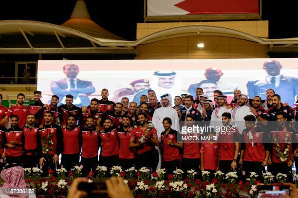 Bahrain's players and staff pose with the trophy during celebrations at Bahrain International Circuit in Sakhir on December 9, 2019 after winning the...