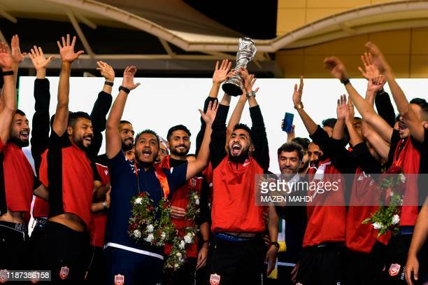 Bahrain's players raise the trophy during celebrations at Bahrain International Circuit in Sakhir on December 9 2019 after winning the 24th Arabian...