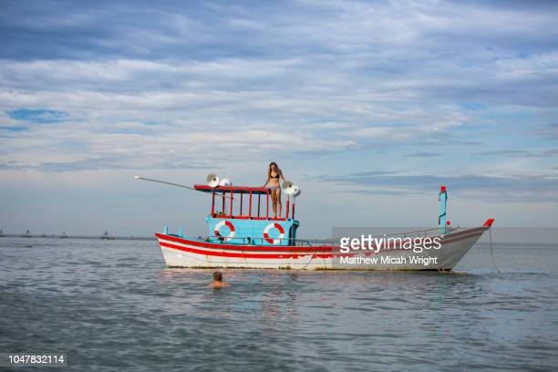 bai xep is a quiet remote fishing village off the tourist path, 10km from the major city of qui nhon. a local fishing boat takes passengers out to explore the islands as tourists jump into the water. - asiatisches langboot stock-fotos und bilder