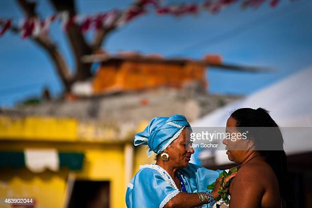 Baiana woman performs a cleansing ritual using the herbs for purification in front of the St Lazarus church on January 30 2012 in Salvador Bahia...
