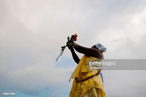 Baiana woman throws flowers in the sea during the celebration of Yemanjá the goddess of the sea in Salvador Bahia Brazil 2 February 2012 Yemanjá...