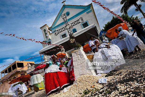 Baiana women perform the popcorn bath an AfroBrazilian spiritual cleansing ritual in front of the St Lazarus church on January 30 2012 in Salvador...