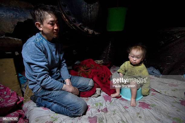 Baigalnaa sits along side his son Munkhorgil, 18 months old while he sits on a baby toilet seat inside the small sewer wher the family lives March...