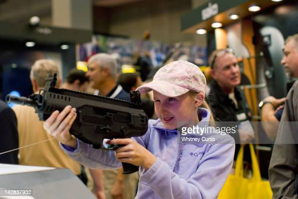 Bailey Chappuis 12yearsold holds a Beretta ARX 160 during the NRA Annual Meetings and Exhibits April 13 2012 at the America's Center in St Louis...