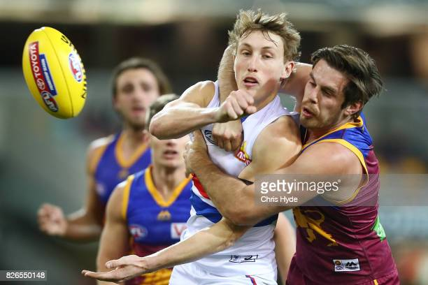 Bailey Dale of the Bulldogs handballs while tackled by Ryan Bastinac of the Lions during the round 20 AFL match between the Brisbane Lions and the...