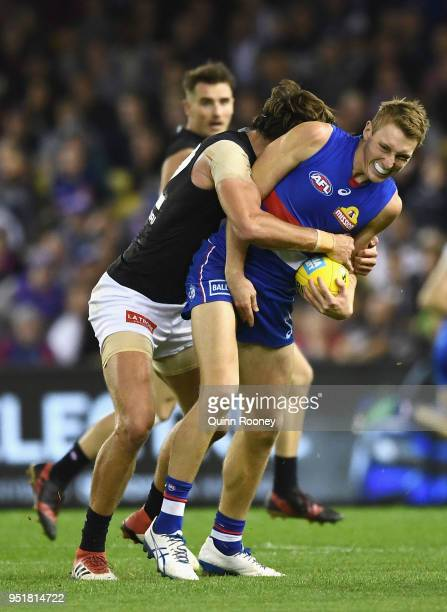 Bailey Dale of the Bulldogs is tackled by Caleb Marchbank of the Blues during the AFL round six match between the Western Bulldogs and Carlton Blues...