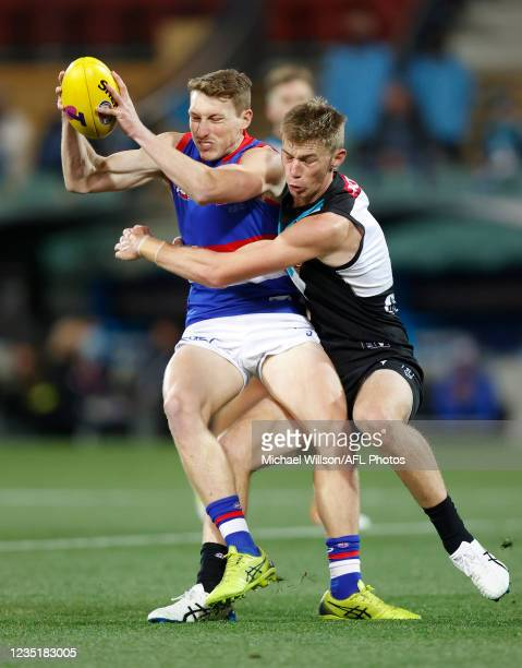 Bailey Dale of the Bulldogs is tackled by Todd Marshall of the Power during the 2021 AFL Second Preliminary Final match between the Port Adelaide...