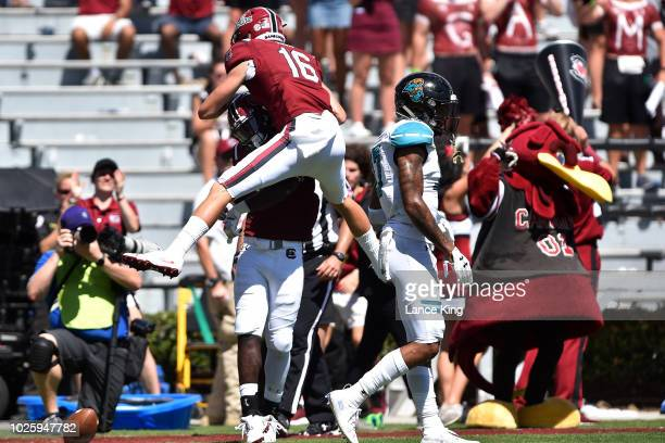 Bailey Hart celebrates with teammate Randrecous Davis of the South Carolina Gamecocks following a 27yard touchdown reception by Davis at...