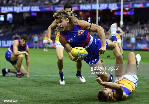 Bailey Smith of the Bulldogs handballs whilst being tackled during the round 2 AFL match between the Western Bulldogs and the West Coast Eagles at...
