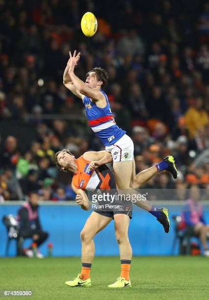 Bailey Williams of the Bulldogs flies over Toby Greene of the Giants during the round six AFL match between the Greater Western Sydney Giants and the...