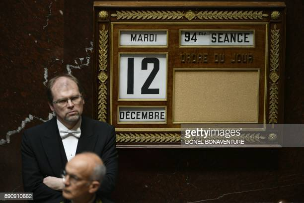 A bailiff stands by a board showing the date and the session number during a session of questions to the Government on December 12 2017 at the...