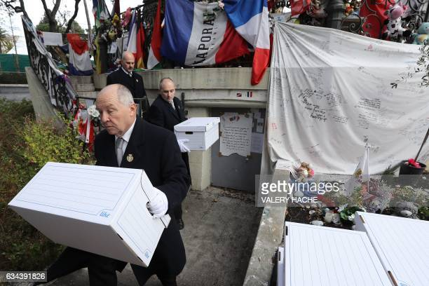 Bailiffs carry and move boxes containing objects dropped off in tribute to victims of the Nice terror attack on February 9 2017 in Nice southeastern...