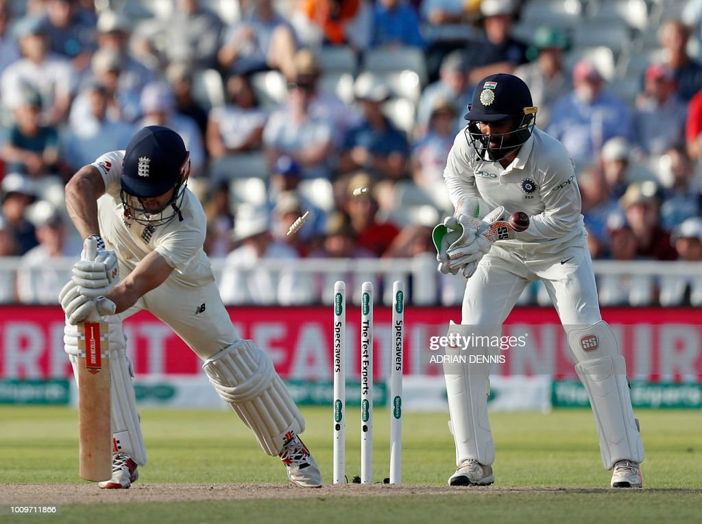 Bails fly as England's Alastair Cook (L) loses his wicket for zero runs in their second innings on the second day of the first Test cricket match between England and India at Edgbaston in Birmingham, central England on August 2, 2018. (Photo by ADRIAN DENNIS / AFP) / RESTRICTED