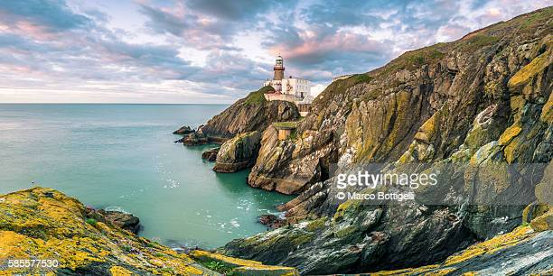 baily lighthouse, howth, county dublin, ireland, europe. panoramic view of the cliff and the lighthouse at sunrise. - dublin stock pictures, royalty-free photos & images