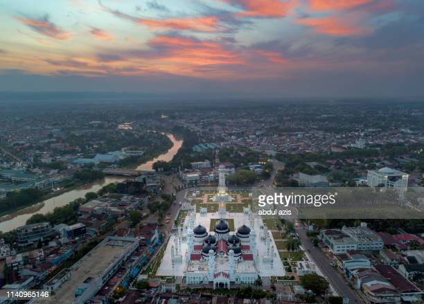 baiturrahman grand mosque burning sunrise, aceh, indonesia - banda aceh stock pictures, royalty-free photos & images