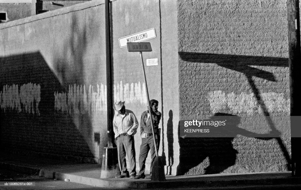 Baja California, Mexico- Mexican men standing on the street corner at sunrise; 2007:11:06
