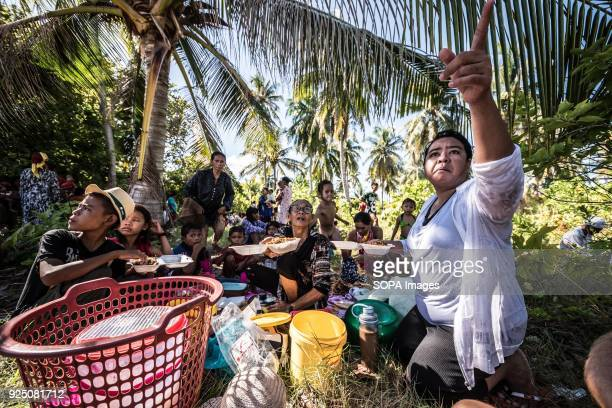 Bajau woman serves food during a water festival held annually by the inhabitants of kalapuan Island. The festival is a purification ritual aimed at...
