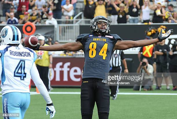 Bakari Grant of the Hamilton Tigercats celebrates a touchdown against the Toronto Argonauts in in a CFL football game at Tim Hortons Field on...