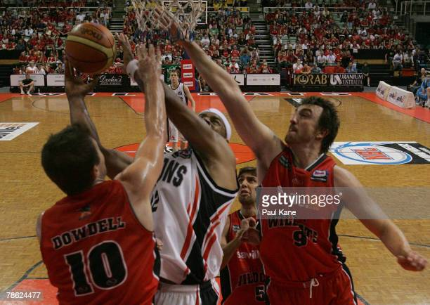 Bakari Hendrix of the Dragons gets his shot blocked by Jeff Dowdell and Paul Rogers of the Wildcats during the round 14 NBL match between the Perth...