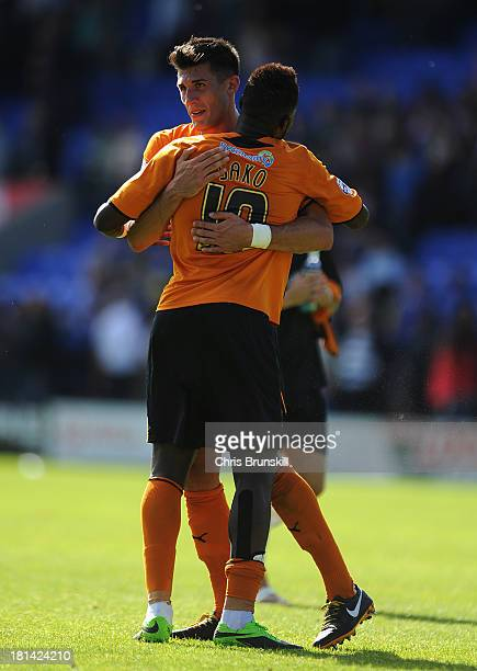 Bakary Sako of Wolverhampton Wanderers embraces teammate Danny Batth following the Sky Bet League One match between Shrewsbury Town and Wolverhampton...