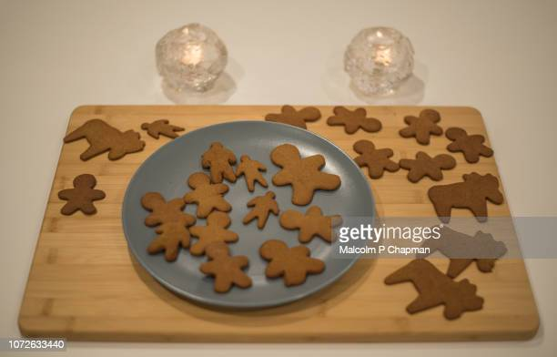 baked and cut gingerbread on a wooden board - swedish culture stock pictures, royalty-free photos & images