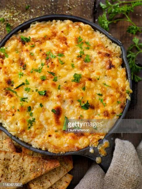 baked artichoke and asiago cheese dip with crispy pita chips - carciofo foto e immagini stock