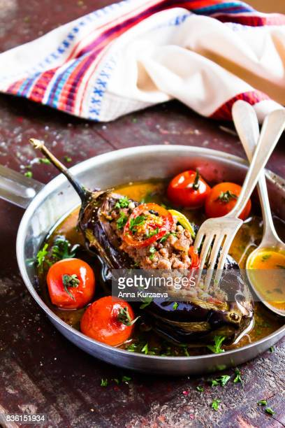 Baked aubergine or eggplant stuffed with minced pork and beef, carrot, pepper, cherry tomatoes in a pan on a wooden table, selective focus