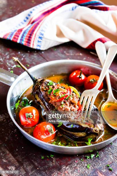baked aubergine or eggplant stuffed with minced pork and beef, carrot, pepper, cherry tomatoes in a pan on a wooden table, selective focus - greek food stock pictures, royalty-free photos & images