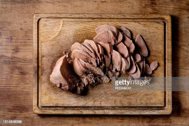 Baked beef tongue sliced. Serving on wooden cutting board over wood background. Flat lay.