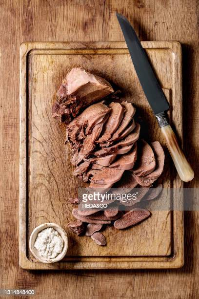 Baked beef tongue sliced. Serving with horseradish sauce and meat knife on wooden cutting board over wood background. Flat lay.