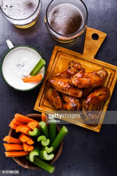 Baked chicken wings with carrots, celery, dipping sauce and beer
