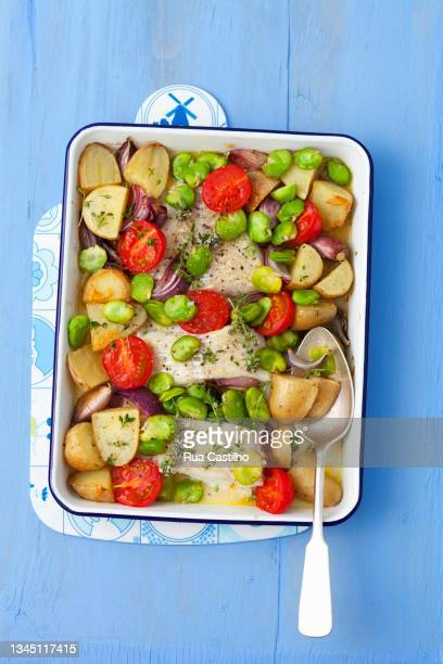 baked cod with potatoes, broad beans, garlic, onions and tomatoes - rua stock-fotos und bilder