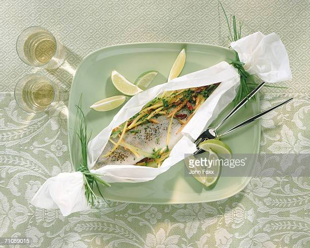 Baked fish with slice of lemon on plate