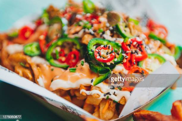 baked fries and nachos with vegan cheese and jalapeños - jalapeno pepper stock pictures, royalty-free photos & images