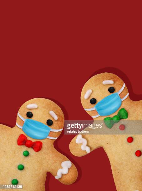 baked gingerbread man cookies with surgical mask - gingerbread men stock pictures, royalty-free photos & images