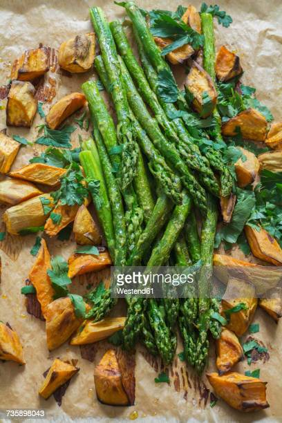 baked green asparagus, sweet potatoes and flat leaf parsley on baking paper - flat leaf parsley stock pictures, royalty-free photos & images