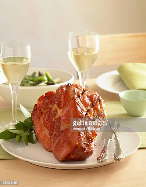 Baked ham with maple-mustard glaze in dinner table setting, close-up