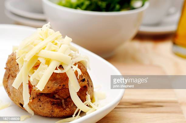 Baked jacket potato with butter and grated cheddar cheese