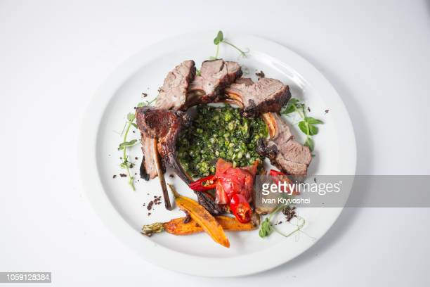 Baked lamb with vegetables on white plate