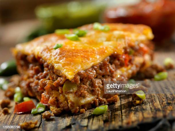 baked, layered, beef taco pie with sour cream, salsa and guacamole - comfort food stock pictures, royalty-free photos & images